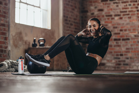 Smiling female in the gym doing sit up