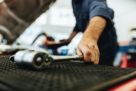 Mechanic picking up a ratchet spanner