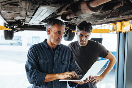 Mechanics using laptop while examining the car