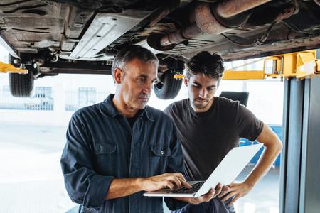 Mechanics using laptop while examining the car