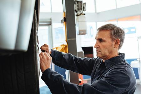 Mechanic replacing wheel of a car in garage