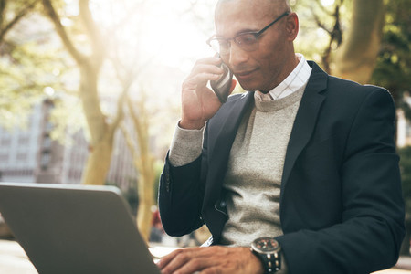 Businessman using laptop and mobile phone sitting outdoors