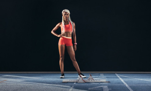 Woman sprinter standing on a running track
