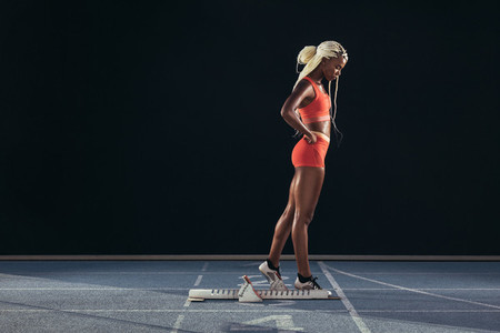 Woman runner standing on a running track