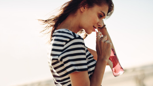 Woman walking outdoors and having a soft drink
