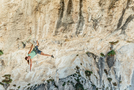 High angle view of rock climber on a overhanging limestone cave resting upsidedown