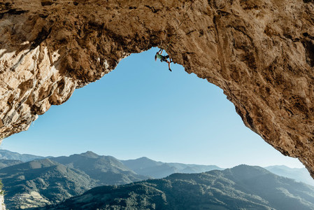Scenic view of rock climber on a overhanging cave at sunset