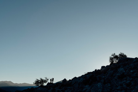 Distant view of couple standing on rock formation during sunset