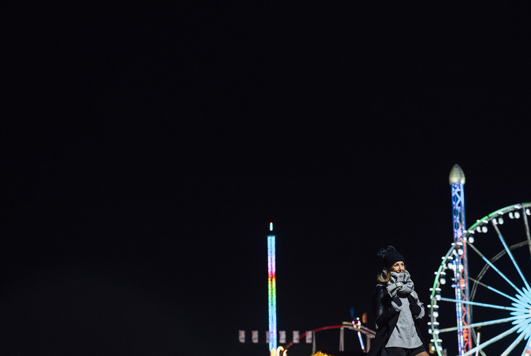 Portrait of a smiling woman  in winter at night with funfair at background