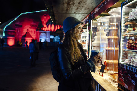 Happy young woman watching a chocolate stand on a funfair at night