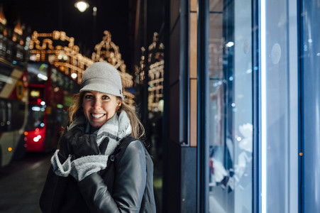 Portrait of a happy young woman at night on London streets  Christmas lights