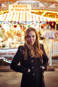 Portrait of a happy young woman on a funfair at night with carousel at backgound