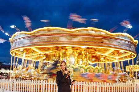 Portrait of a young woman using smart phone on a funfair at night with carousel at backgound