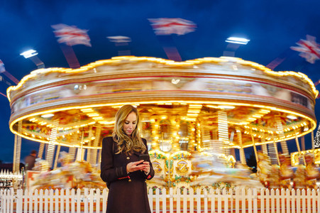 Young woman using smart phone on a funfair at night with carousel at backgound