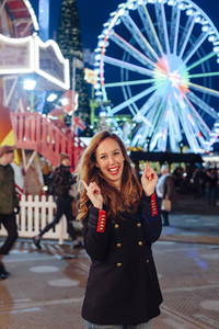 Portrait of a happy young woman on a funfair at night