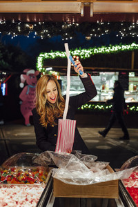 Happy young woman on a funfair at night buying jelly beans