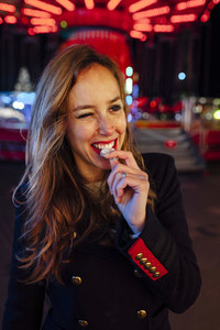 Happy young woman on a funfair at night eating jelly beans