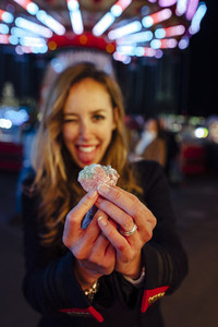 Happy young woman on a funfair at night showing jelly beans
