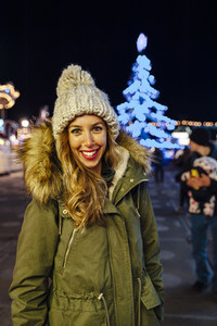 Portrait of a young woman at night with illuminated Christmas tree on background