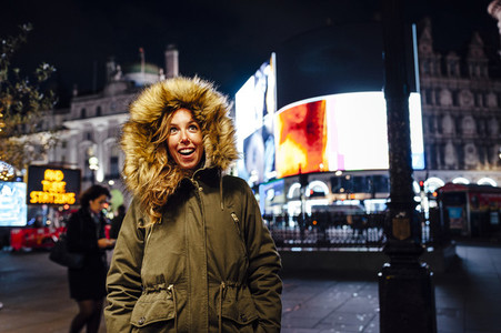 Young woman enjoying Christmas lights in Picadilly Circus London