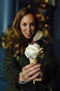 Young blonde woman showing ice cream at night with Christmas lights