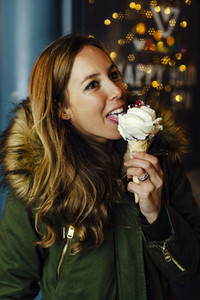Young blonde woman eating ice cream at night with Christmas lights
