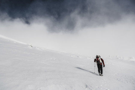 A man wearing red jacket and a backpack trekking in the snow on a foggy day
