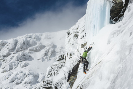 A man in green jacket and sunglasses ice climbing up through a icefall