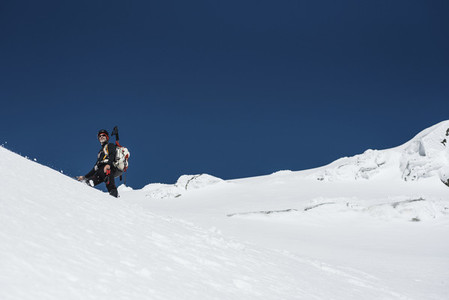Portrait of a man trekking in the snow on a sunny day