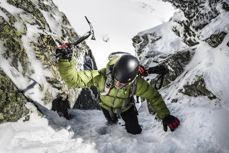A man in green jacket and helmet climbing up through the snow with a iceaxe