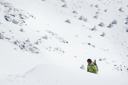 A man wearing green jacket and a backpack trekking in the snow on a sunny day