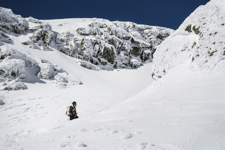 A man with backpack trekking in the snow on a sunny day