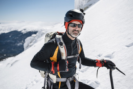 Portrait of a man with backpack and helmet trekking in the snow on a sunny day