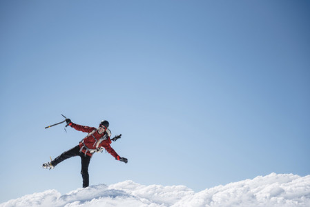 Portrait of a man celebrating the summit of a mountain in the snow on a sunny day