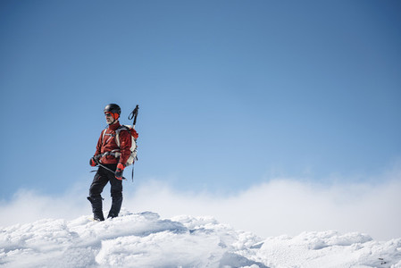 Portrait of a man looking at horizon in the summit of a mountain in the snow on a sunny day