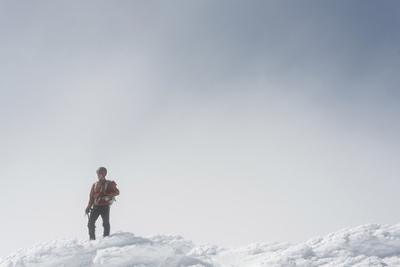 Portrait of a man looking at horizon in the summit of a mountain in the snow on a foggy day