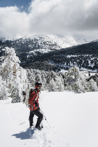 Portrait of a man looking at horizon on a mountain with snow on a sunny day