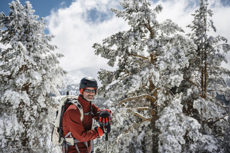 Portrait of a man looking at camera on a mountain with snow and pine trees on a sunny day