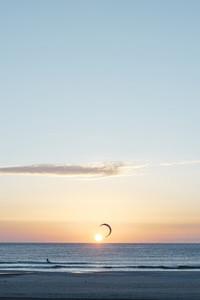 Man kitesurfing on windy day at sunset
