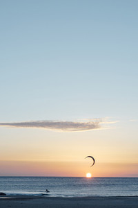 Man kitesurfing on windy day at sunset