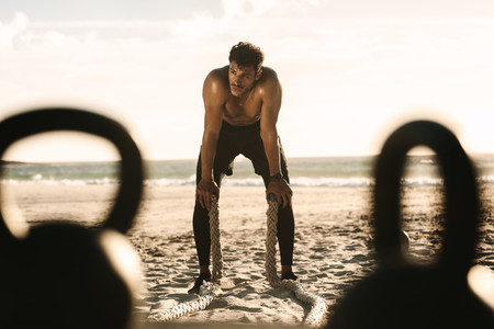 Man doing fitness training at the beach with battle ropes and ke