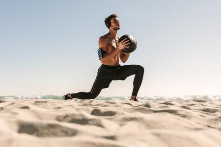 Man training at the beach using a medicine ball