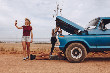 Women with broken down car on road trip