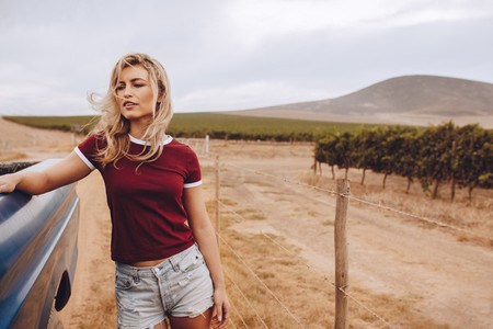Woman on road trip standing by a truck