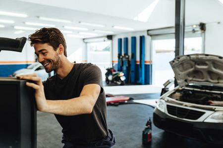 Smiling mechanic doing car diagnostic on computer