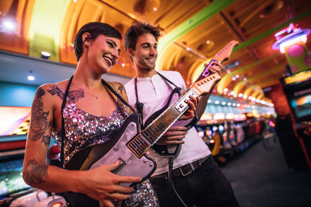 Couple playing guitar arcade game looking at the console