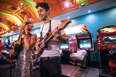 Excited couple holding gaming guitars in hand having fun