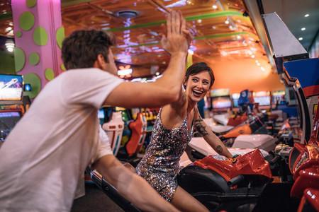 Couple playing racing games sitting on arcade racing bikes