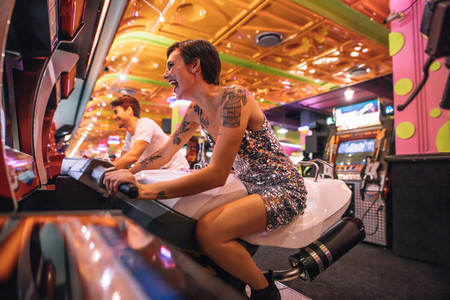 Couple playing an arcade racing game sitting on bikes