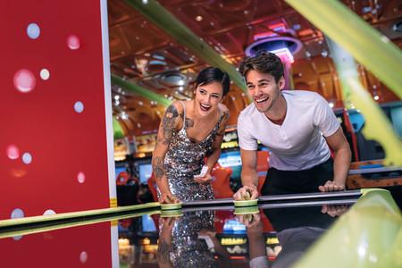 Man and woman playing air hockey game at a gaming parlour